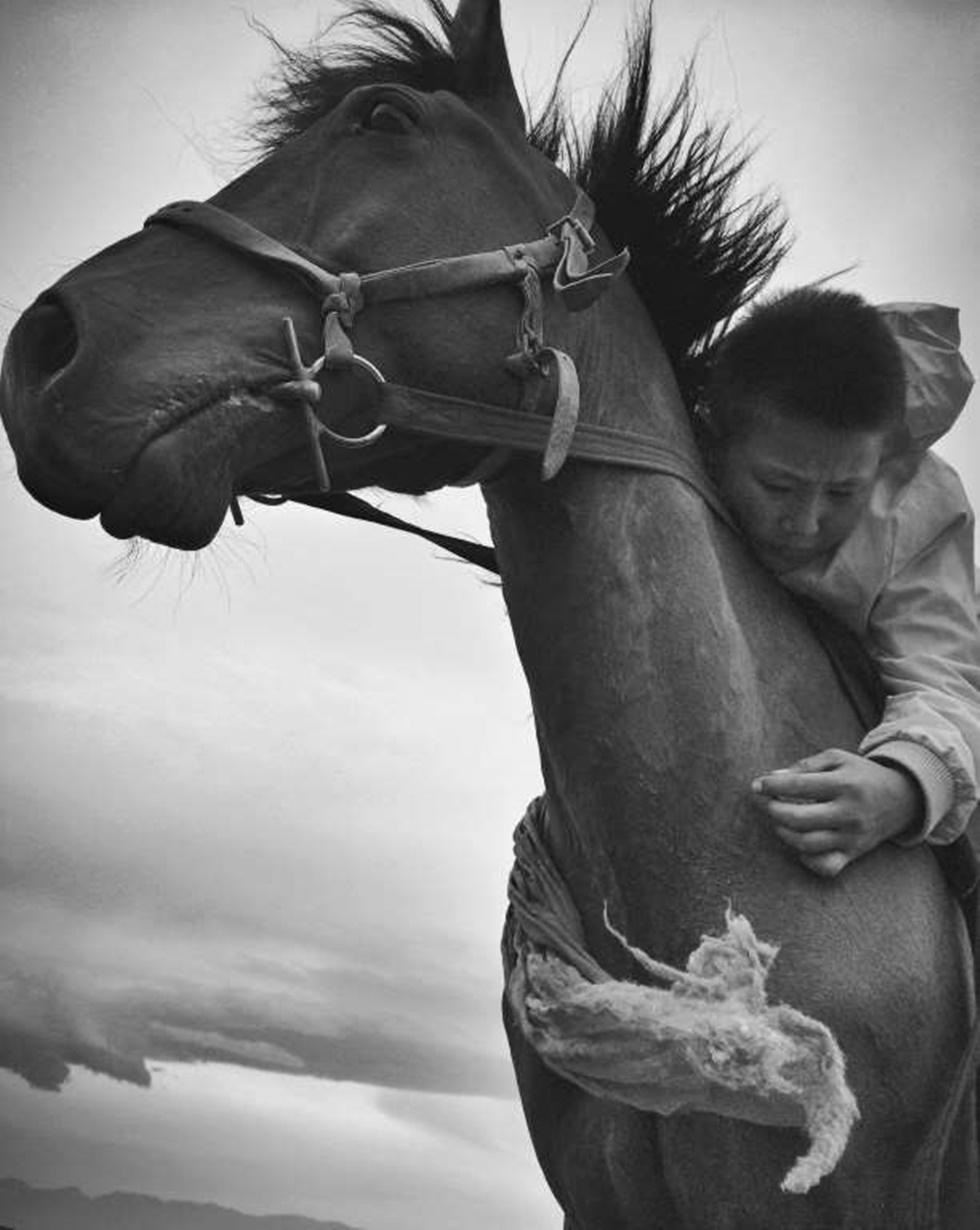 """SEGUNDO LUGAR, NIÑOS """"Esta es la tribu Tours Hu, un condado autónomo mongol en la provincia más remota de Xinjiang, ciudad natal de Donggui. El festival de Namuda es espectacular, especialmente las carreras de caballos. Cuando el niño ganó se sentía tan real como convertirse en un rey. Los ancianos, incluido su abuelo, llevarán a su caballo alrededor de la audiencia para celebrar el momento.""""."""