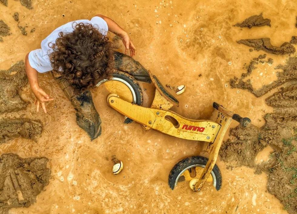 """TERCER LUGAR, NIÑOS """"Esta foto fue tomada en una zona rural de Río llamada Vargem Grande, donde Felipe, de 3 años y mi hijo mayor, le encanta explorar la pista de motocross con su moto de madera. La lluvia que no podía resistir saltar en ella.""""."""