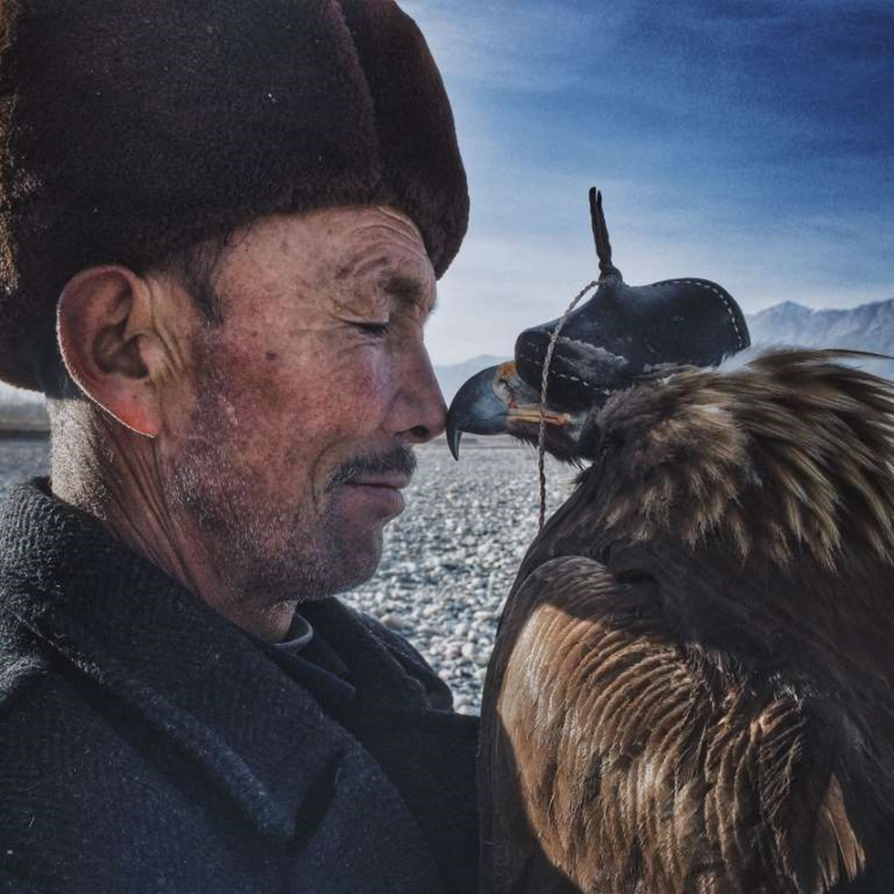 """""""Los valientes y sabios Khalkhas viven a lo largo de las montañas en el sur de Xinjiang y son compañeros de las águilas. Consideran águilas como sus hijos y los entrenan durante muchos años para cazar. Este hombre de 70 años es rígido y solemne delante de su familia y amigos, pero cuando está con su amado águila, la esquina de su boca se curva. Cuando las águilas llegan a la edad de apareamiento, aunque él es muy renuente, el hombre libera las águilas de nuevo en la naturaleza de modo que puedan prosperar. Un corazón suave y un amor exquisito están cubiertos por su rostro golpeado por el tiempo. Es un hombre duro con un corazón tierno""""."""