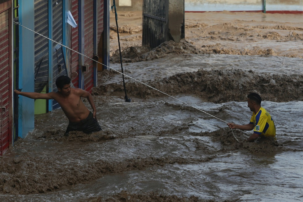 A man helps another man cross a flooded street after a massive landslide and flood in the Huachipa district of Lima, Peru March 17, 2017. REUTERS/Guadalupe Pardo