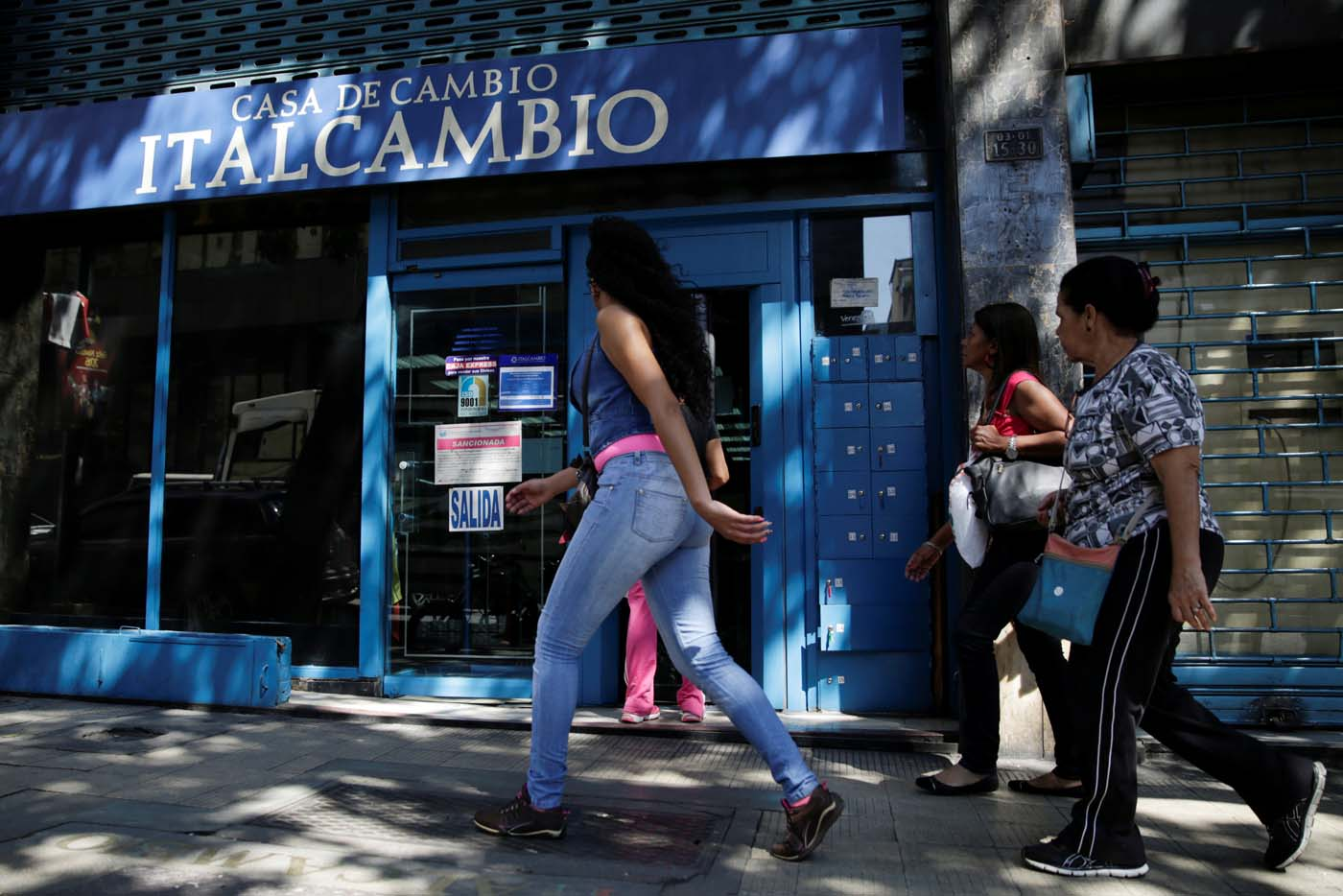 People walk past a branch of Italcambio currency exchange in Caracas, Venezuela January 20, 2017. Picture taken January 20, 2017. REUTERS/Marco Bello To match Exclusive VENEZUELA-BANKS/