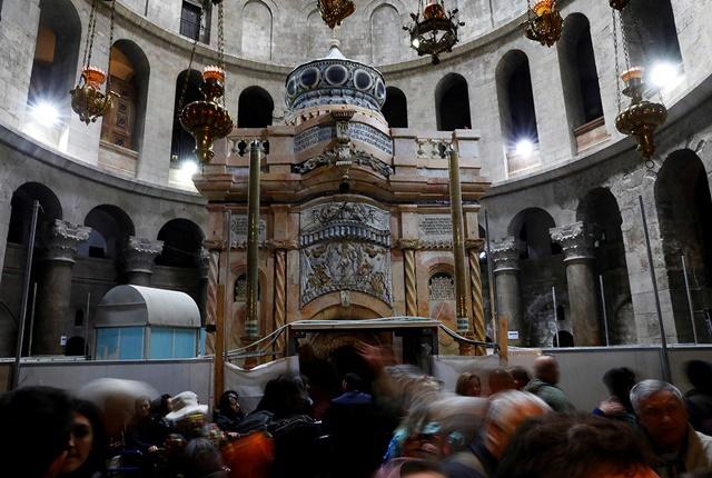 Visitantes cerca del recién restaurado edículo en la iglesia del Santo Sepulcro de Jerusalén, Israel, el 20 de marzo de 2017.