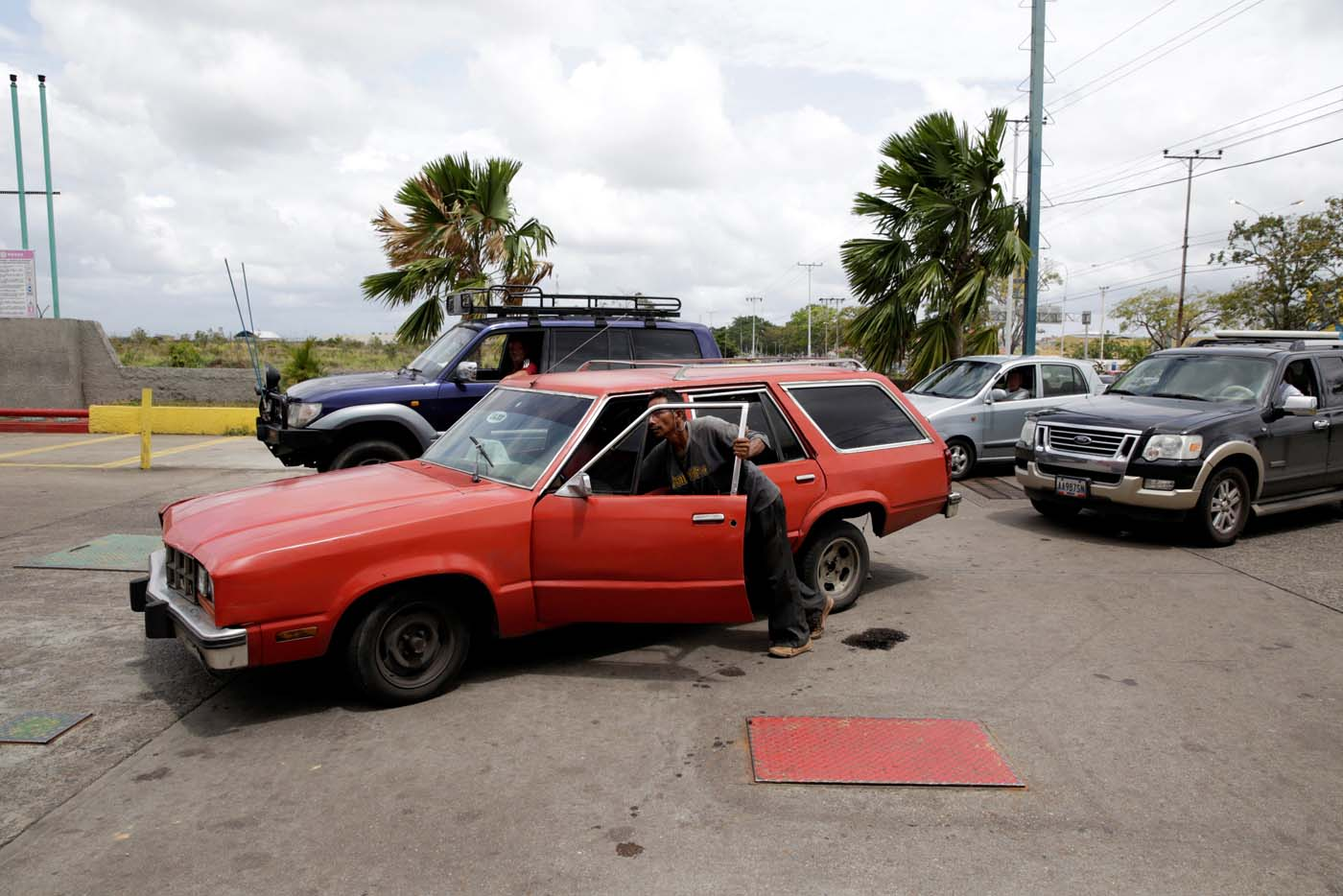 A man pushes his car after running out of gas at a gas station of Venezuelan state oil company PDVSA in Maturin, Venezuela March 23, 2017. REUTERS/Marco Bello
