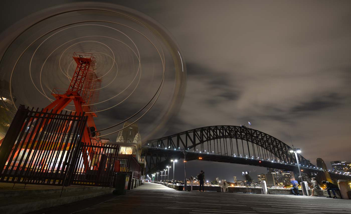 The ferris wheel at Luna Park and Sydney Harbour Bridge are plunged into darkness for the Earth Hour environmental campaign in Sydney on March 25, 2017. The lights went out on two of Sydney's most famous landmarks for the 10th anniversary of the climate change awareness campaign Earth Hour, among the first landmarks around the world to dim their lights for the event. / AFP PHOTO / PETER PARKS