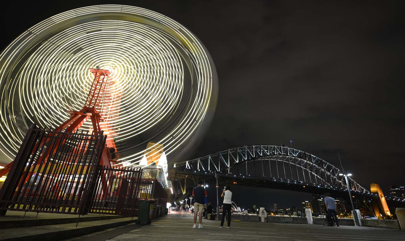 The ferris wheel at Luna Park and Sydney Harbour Bridge are seen before being plunged into darkness for the Earth Hour environmental campaign in Sydney on March 25, 2017. The lights went out on two of Sydney's most famous landmarks for the 10th anniversary of the climate change awareness campaign Earth Hour, among the first landmarks around the world to dim their lights for the event. / AFP PHOTO / PETER PARKS