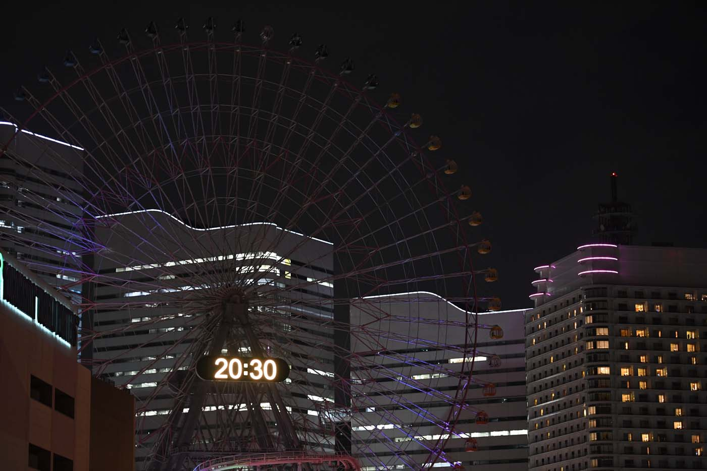 The Yokohama giant ferris wheel, Cosmo Clock 21, is seen with its lights turned off for the Earth Hour environmental campaign in Yokohama on March 25, 2017. / AFP PHOTO / Toshifumi KITAMURA