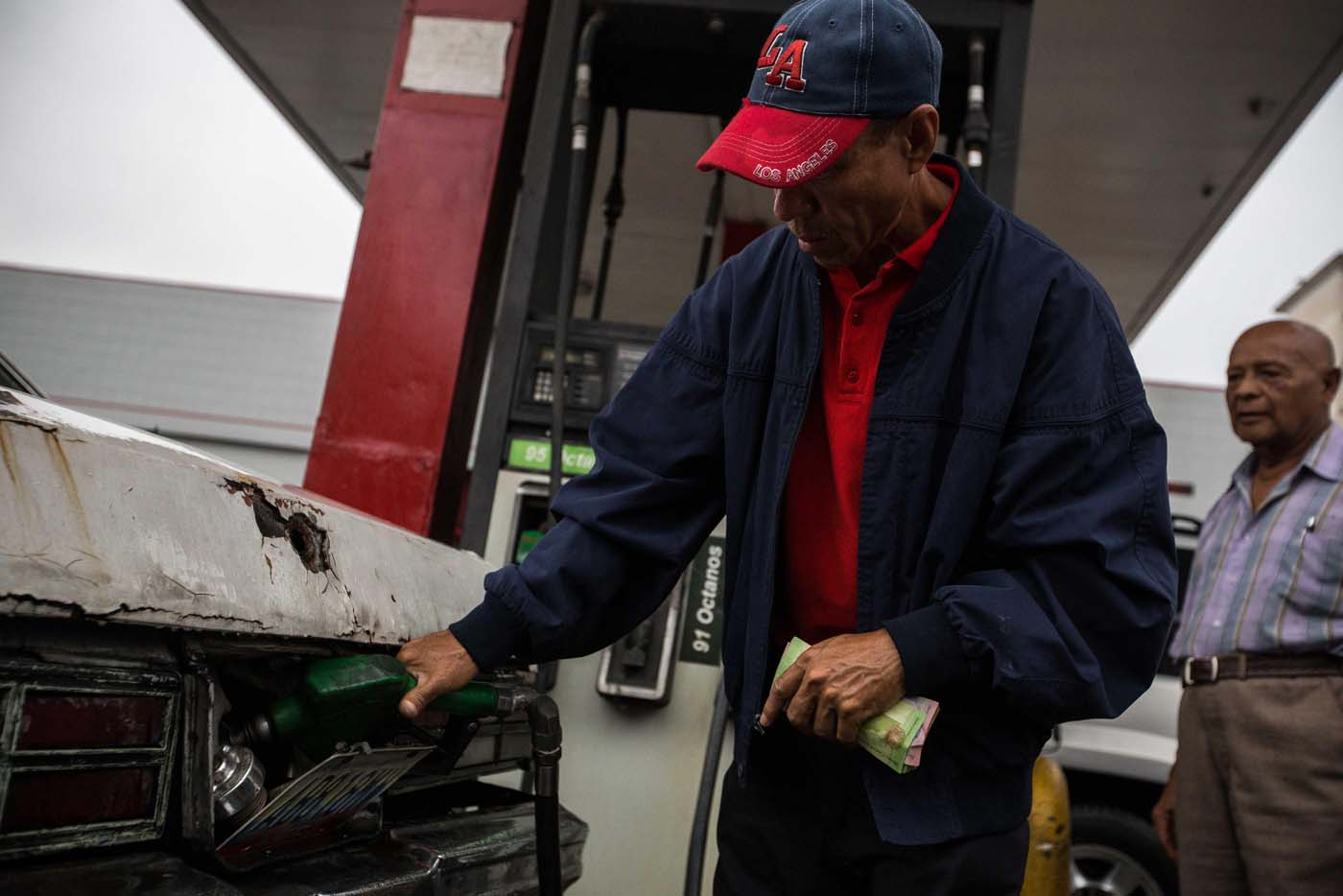 CAR303. CARACAS (VENEZUELA), 24/03/2017.- Un hombre llena el tanque de combustible de un vehículo hoy, viernes 24 de marzo de 2017, en una estación de gasolinaen Caracas (Venezuela). Decenas de estaciones de servicio en Venezuela amanecieron hoy con vehículos en cola para abastecerse de gasolina, luego de que la estatal Pdvsa reportara el pasado miércoles un retraso en el transporte de combustible y se registrasen fallos de suministro en al menos cuatro estados centrales. EFE/CRISTIAN HERNÁNDEZ
