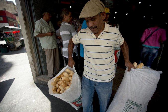 Un empleado de la panadería Minka, intervenida por el Estado, lleva bolsas de pan para ser distribuidas a tiendas estatales en Caracas. Credit Fernando Llano/Associated Press