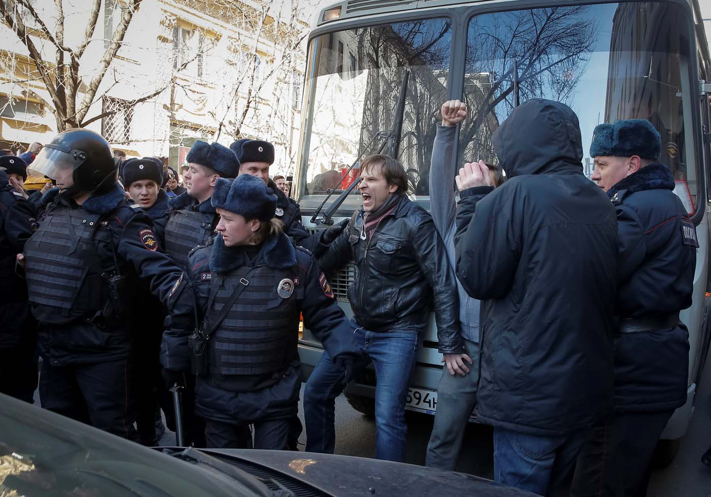 An opposition supporter (C) blocks a police van transporting detained anti-corruption campaigner and opposition figure Alexei Navalny during a rally in Moscow, Russia, March 26, 2017. REUTERS/Maxim Shemetov
