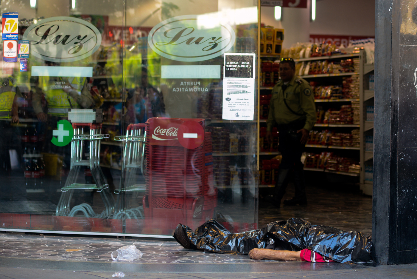 The body of a man lies outside a supermarket, where he died of a heart attack after waiting in a long line to buy food, in Caracas on March 30, 2017. / AFP PHOTO / FEDERICO PARRA