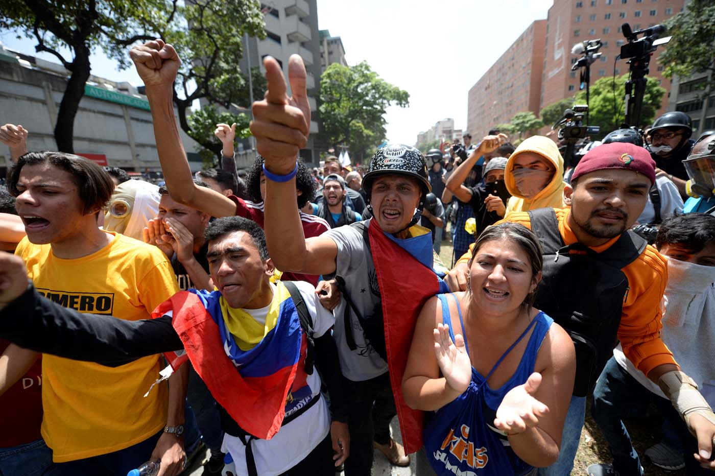 """Venezuelan opposition activists demonstrate during a protest in Caracas on April 4, 2017. Venezuela has been mired in turmoil since the Supreme Court last week tried to tighten Maduro's grip on power by assuming legislative powers from the National Assembly -- a move opponents had angrily branded as a """"coup d'etat."""" / AFP PHOTO / FEDERICO PARRA"""