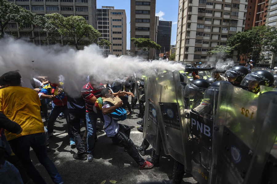 Venezuela's opposition activists clash with riot police agents during a protest against Nicolas Maduro's government in Caracas on April 4, 2017. Protesters clashed with police in Venezuela Tuesday as the opposition mobilized against moves to tighten President Nicolas Maduro's grip on power. Protesters hurled stones at riot police who fired tear gas as they blocked the demonstrators from advancing through central Caracas, where pro-government activists were also planning to march.  / AFP PHOTO / JUAN BARRETO