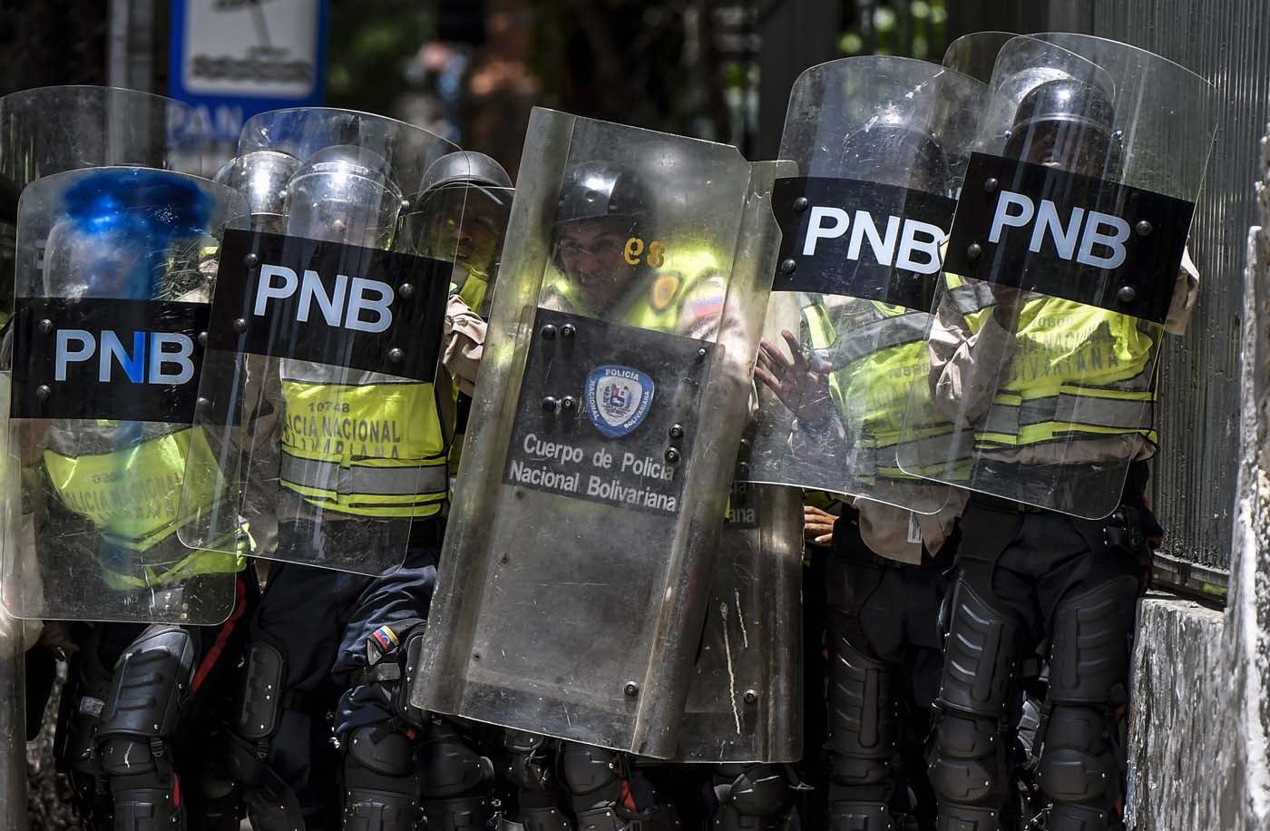 Bolivarian police agents hold their shields and prepare for confrontation during a protest against Nicolas Maduro's government in Caracas on April 4, 2017. Protesters clashed with police in Venezuela Tuesday as the opposition mobilized against moves to tighten President Nicolas Maduro's grip on power. Protesters hurled stones at riot police who fired tear gas as they blocked the demonstrators from advancing through central Caracas, where pro-government activists were also planning to march. / AFP PHOTO / JUAN BARRETO