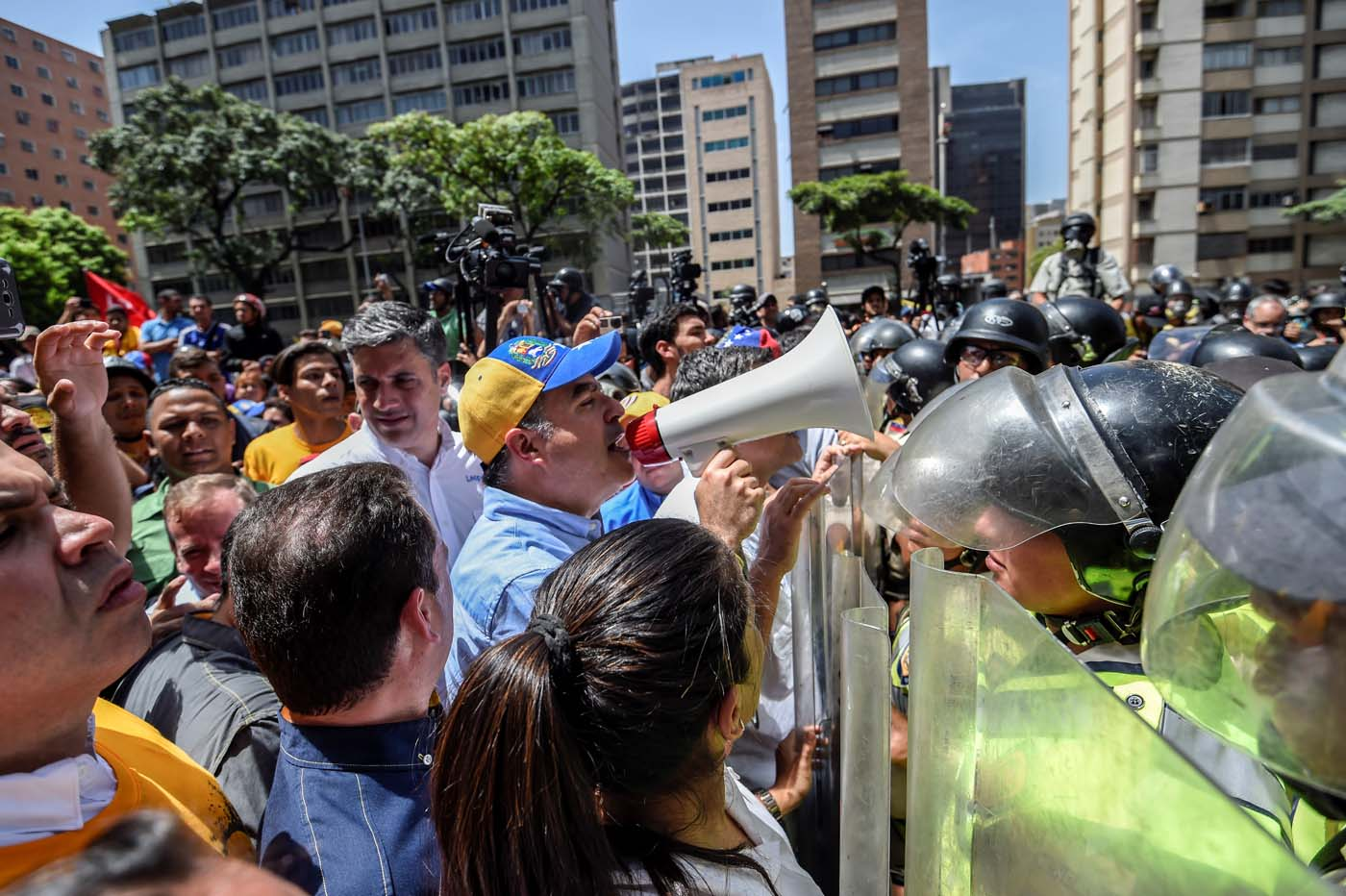 The President of the National Assembly Julio Borges using a megaphone addresses riot police agents during a protest against Nicolas Maduro's government in Caracas on April 4, 2017. Protesters clashed with police in Venezuela Tuesday as the opposition mobilized against moves to tighten President Nicolas Maduro's grip on power. Protesters hurled stones at riot police who fired tear gas as they blocked the demonstrators from advancing through central Caracas, where pro-government activists were also planning to march. / AFP PHOTO / JUAN BARRETO