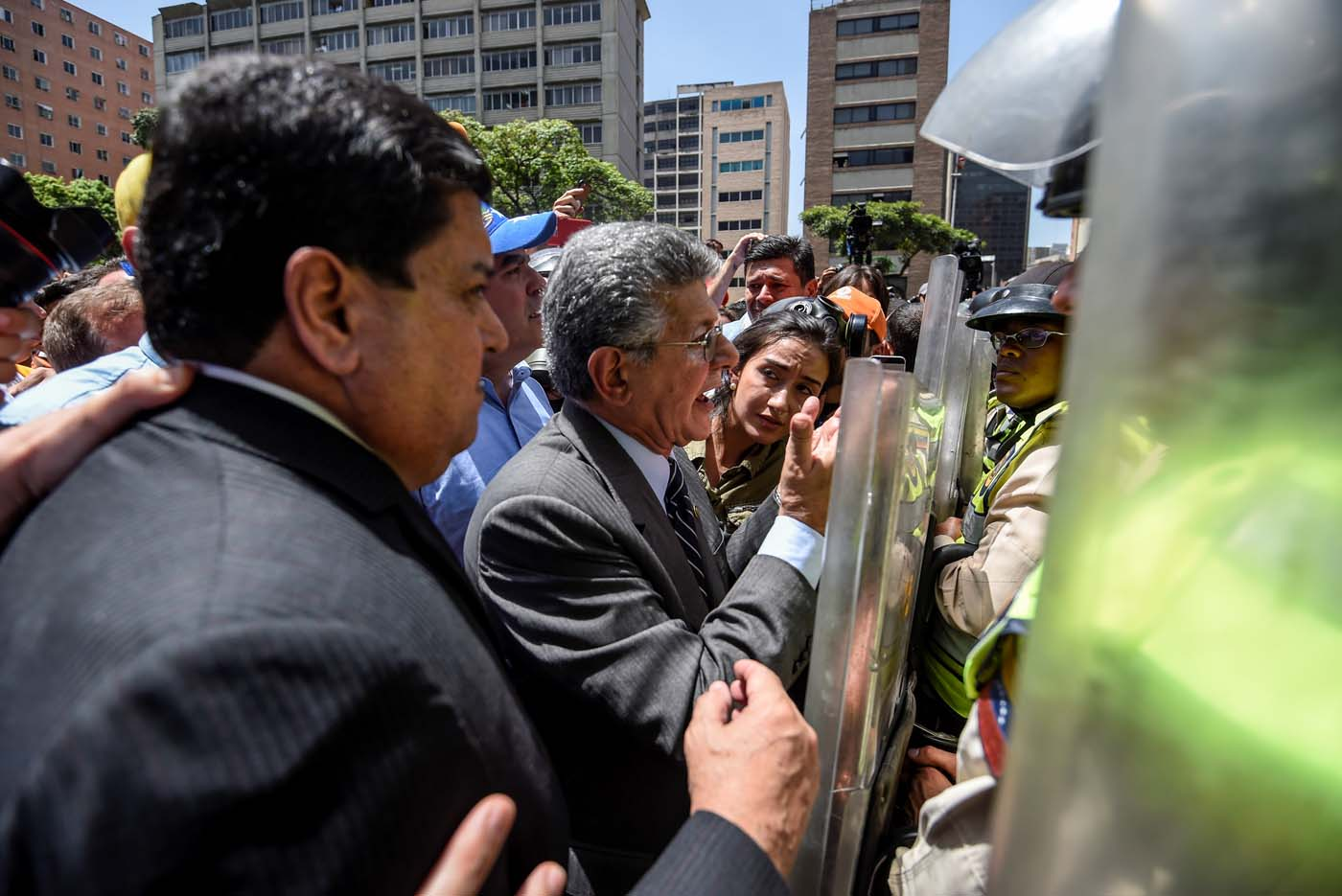 Former President of the Venezuelan National Assembly Henry Ramos Allup(C) speaks with riot police officers during a protest against Nicolas Maduro's government in Caracas on April 4, 2017. Protesters clashed with police in Venezuela Tuesday as the opposition mobilized against moves to tighten President Nicolas Maduro's grip on power. Protesters hurled stones at riot police who fired tear gas as they blocked the demonstrators from advancing through central Caracas, where pro-government activists were also planning to march. / AFP PHOTO / JUAN BARRETO