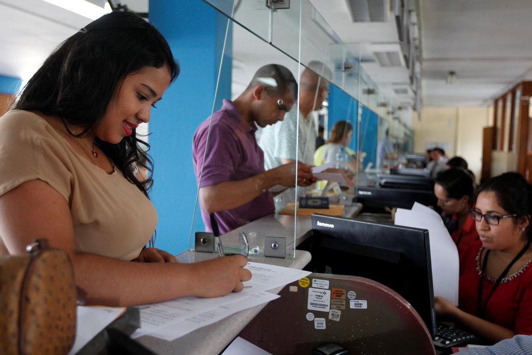 Una ciudadana venezolana firma documentos para obtener su Permiso Temporal de Permanencia en Perú el 6 de febrero de 2017. Credit Guadalupe Pardo/Reuters