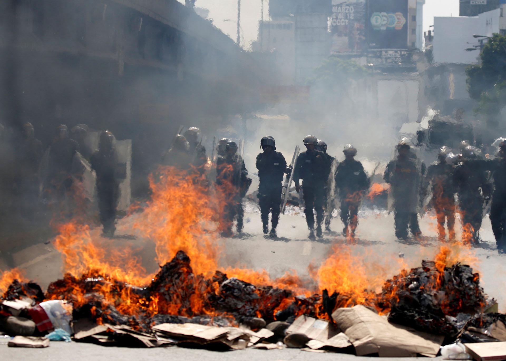 Venezuelan national guards are seen through a burning barricade during an opposition rally in Caracas, Venezuela, April 6, 2017. REUTERS/Carlos Garcia Rawlins