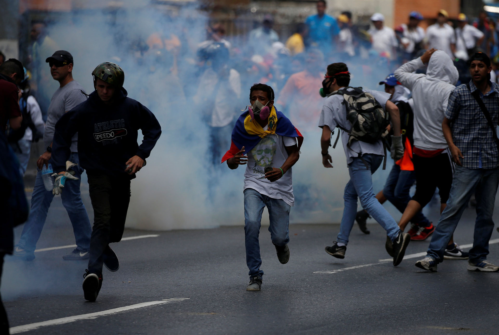 Demonstrators run away from tear gas fired by security forces during an opposition rally in Caracas, Venezuela April 6, 2017. REUTERS/Carlos Garcia Rawlins