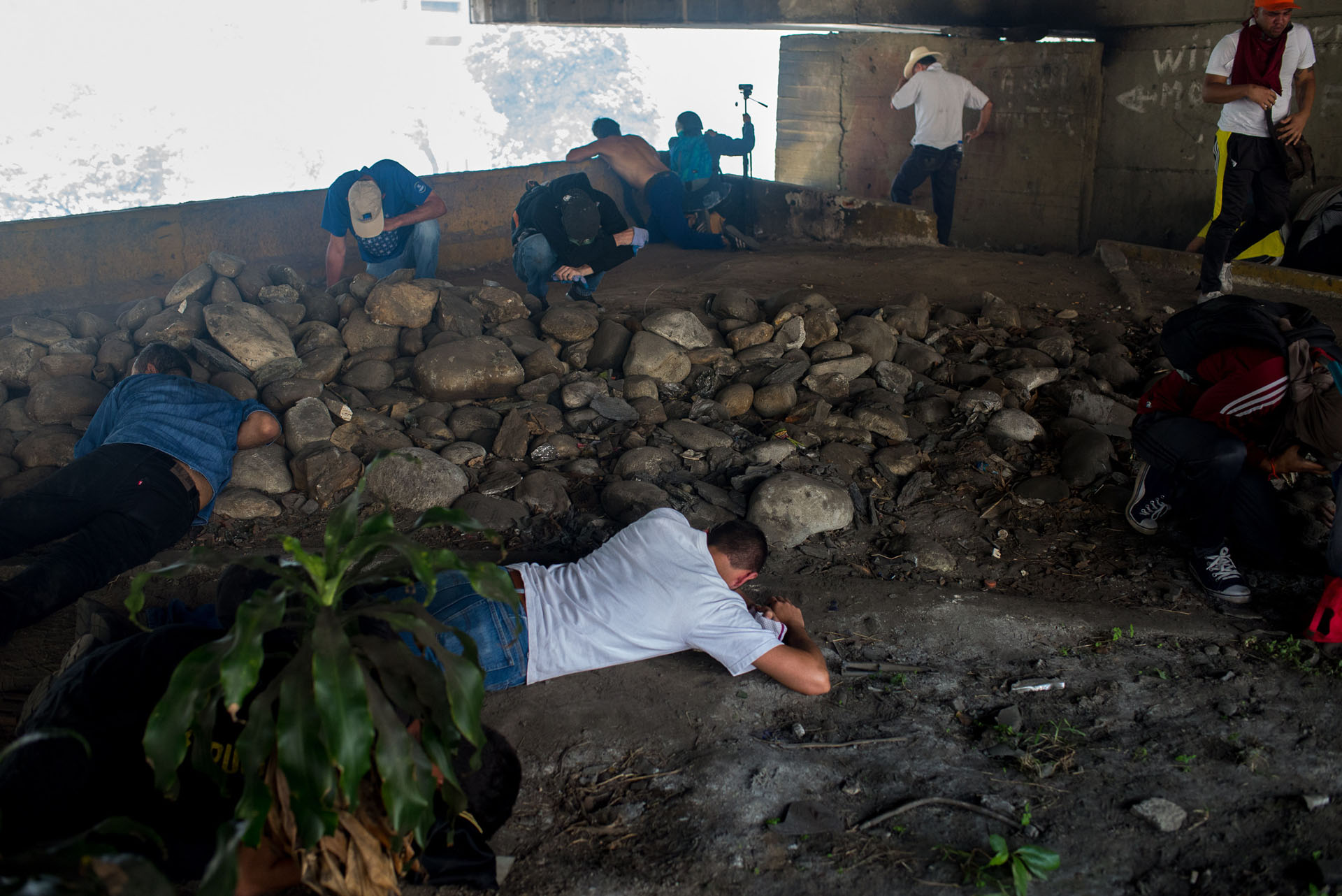 CAR01. CARACAS (VENEZUELA), 06/04/2017 - Manifestantes opositores se cubren del gas lacrimógeno durante una manifestación de opositores al gobierno de Nicolás Maduro hoy, jueves 6 de abril de 2017, en Caracas (Venezuela). Dos fotógrafos de la Agencia EFE en Caracas resultaron hoy heridos durante una protesta opositora en Caracas cuando agentes de los cuerpos de seguridad dispararon a quemarropa contra ellos mientras cubrían gráficamente la manifestación en el este de la capital venezolana. EFE/Manaure Quintero