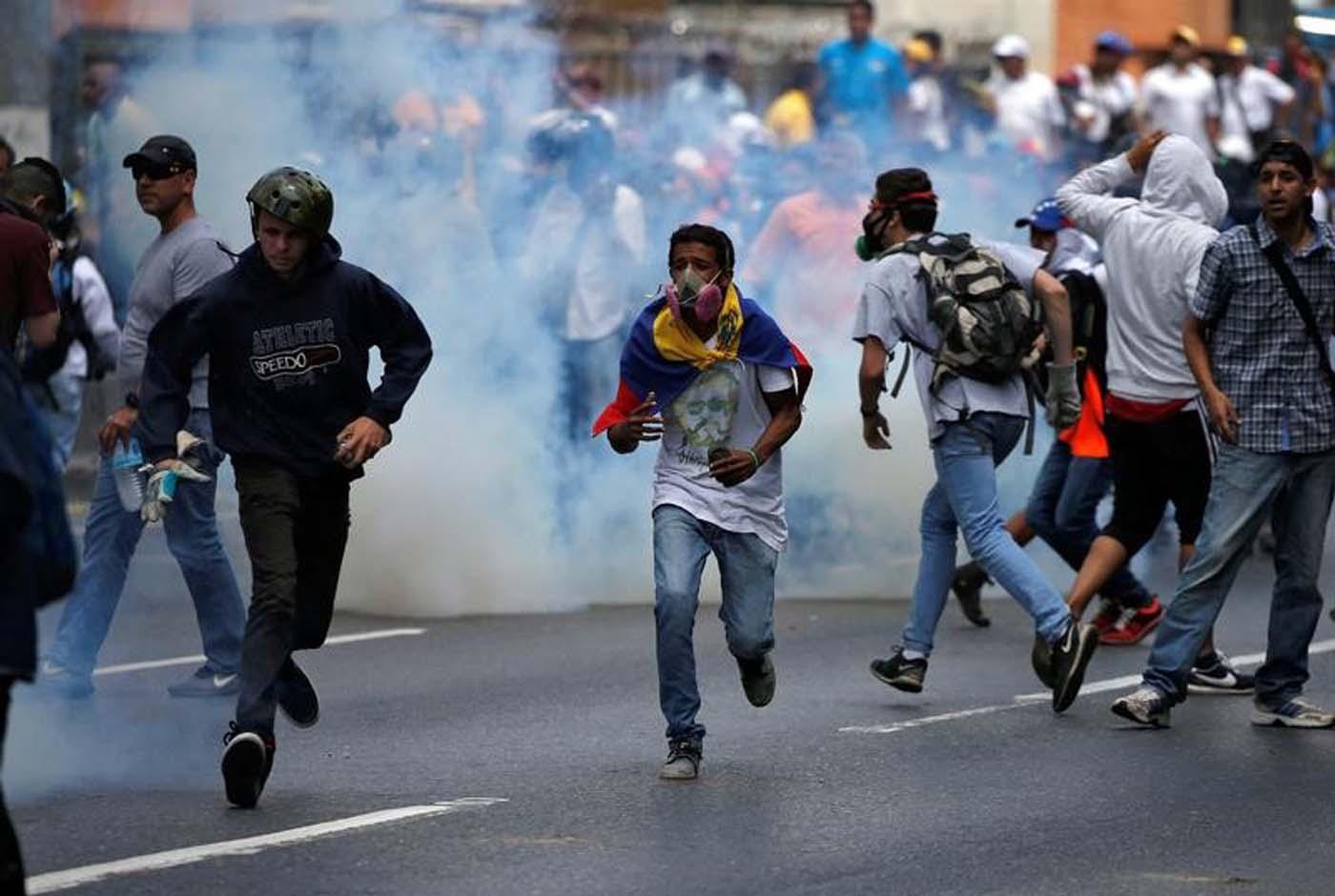 Manifestantes huyen de las fuerzas de seguridad que dispararon gases lacrimógeno durante una marcha de la oposición en Caracas. 6 de abril de 2017. Fuerzas de seguridad bloqueaban el jueves el paso de una marcha opositora en Caracas que reclamaba la destitución de jueces del máximo tribunal, que habían suspendido las funciones parlamentarias, una medida que generó protestas y exhortos internacionales a respetar la separación de poderes. REUTERS/Carlos Garcia Rawlins