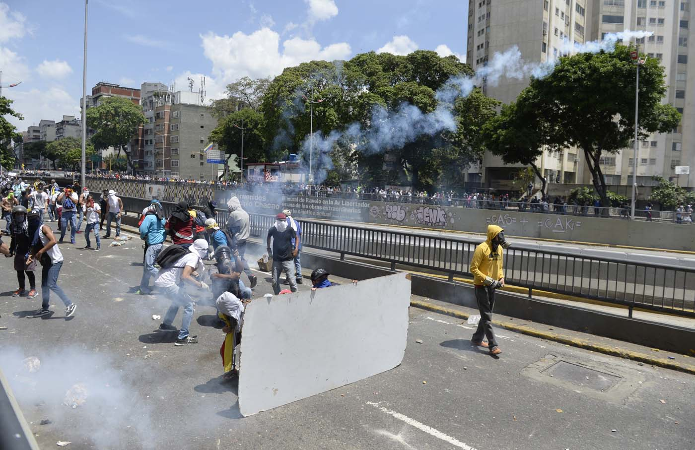 "Demonstrators against Nicolas Maduro's government clash with riot police eastern Caracas on April 8, 2017. The opposition is accusing pro-Maduro Supreme Court judges of attempting an internal ""coup d'etat"" for attempting to take over the opposition-majority legislature's powers last week. The socialist president's supporters held counter-demonstrations on Thursday, condemning Maduro's opponents as ""imperialists"" plotting with the United States to oust him. / AFP PHOTO / FEDERICO PARRA"