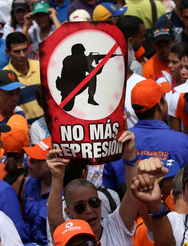 People participate in an opposition rally in Caracas, Venezuela, April 8, 2017. The sign reads