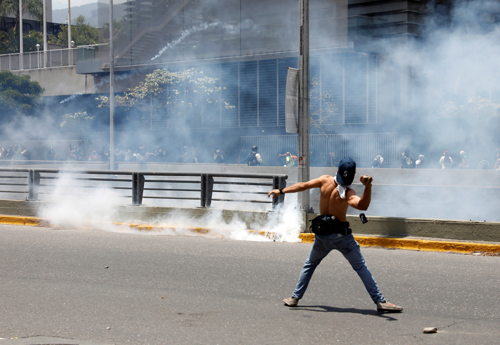 A demonstrator throws stones during clashes with the police during an opposition rally in Caracas, Venezuela, April 8, 2017. REUTERS/Carlos Garcia Rawlins