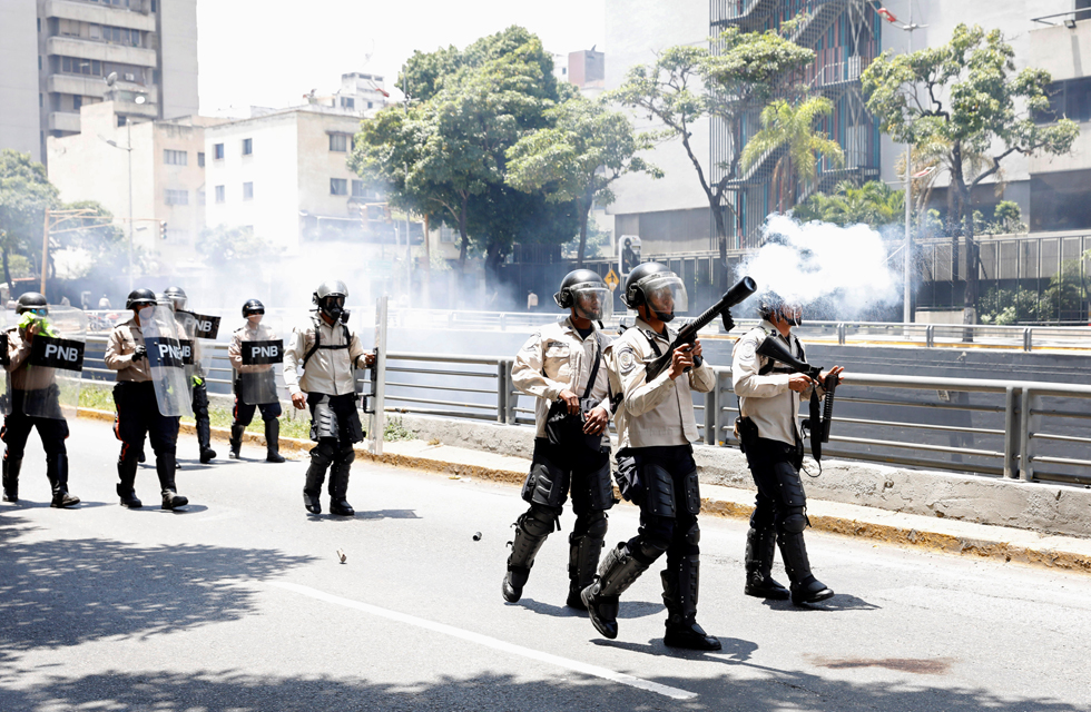 Riot police offcer fires a gas canister during an opposition rally in Caracas, Venezuela, April 8, 2017. REUTERS/Carlos Garcia Rawlins