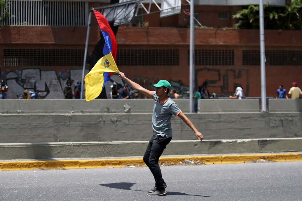 A demonstrator holds a Venezuelan flag during clashes with riot police during a rally in Caracas, Venezuela, April 8, 2017. REUTERS/Carlos Garcia Rawlins
