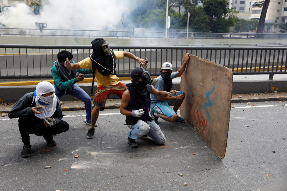Demonstrators prepare to throw rocks as they clash with riot police during a rally in Caracas, Venezuela, April 8, 2017. REUTERS/Carlos Garcia Rawlins
