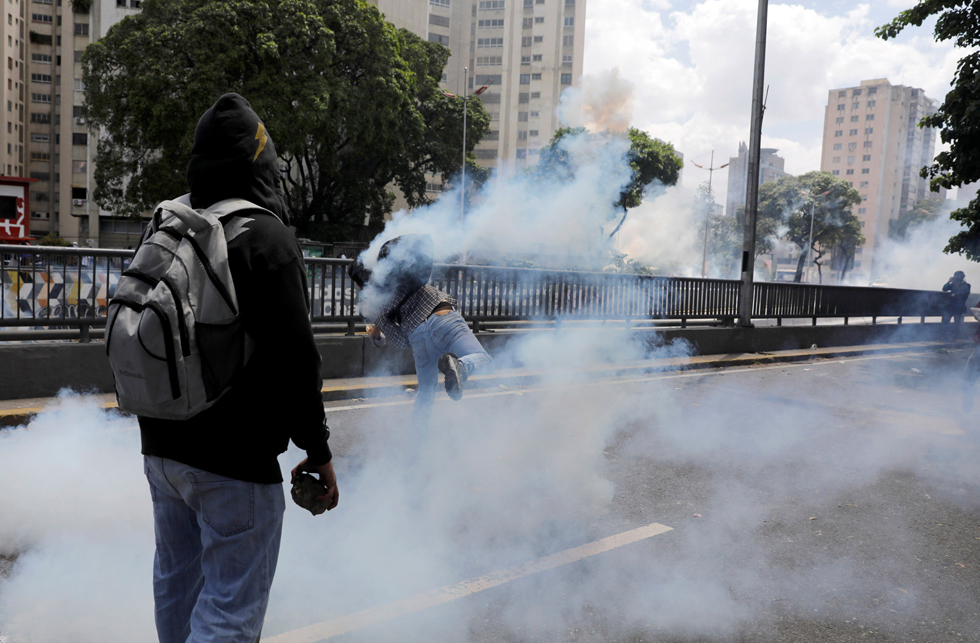 REFILE - CLARIFYING CAPTIONA demonstrator throws back a tear gas canister during clashes with riot police during a rally in Caracas, Venezuela, April 8, 2017. REUTERS/Carlos Garcia Rawlins