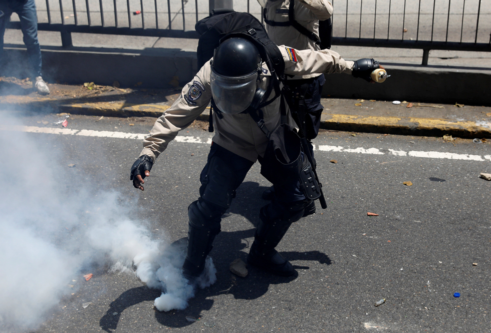 REFILE - CLARIFYING CAPTIONA riot police officer attempts to kick a tear gas canister during clashes with opposition supporters in Caracas, Venezuela, April 8, 2017. REUTERS/Carlos Garcia Rawlins