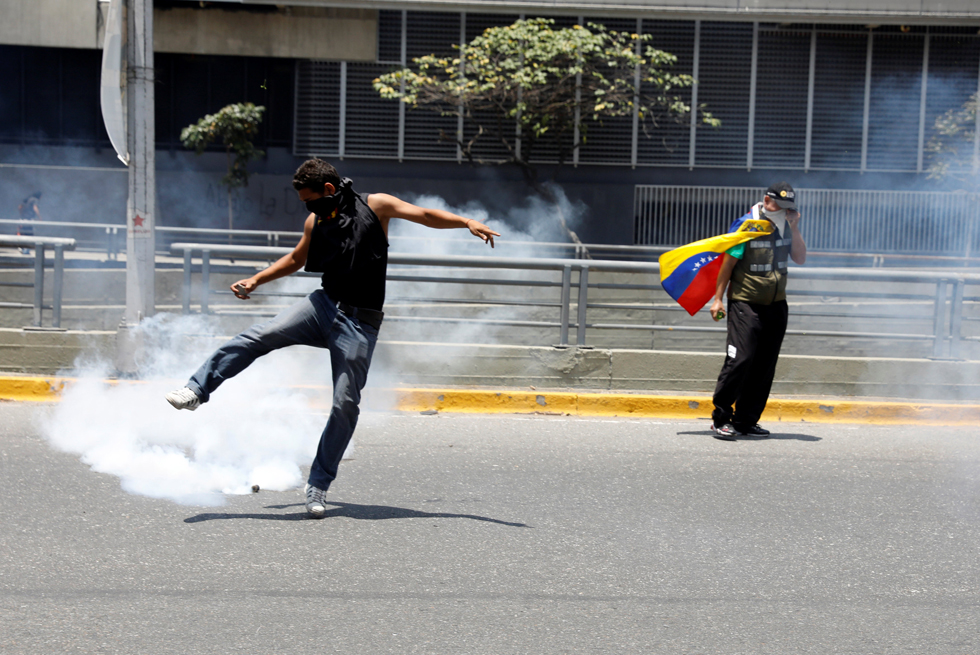 REFILE - CLARIFYING CAPTIONA demonstrator kicks a tear gas canister during an opposition rally in Caracas, Venezuela, April 8, 2017. REUTERS/Carlos Garcia Rawlins