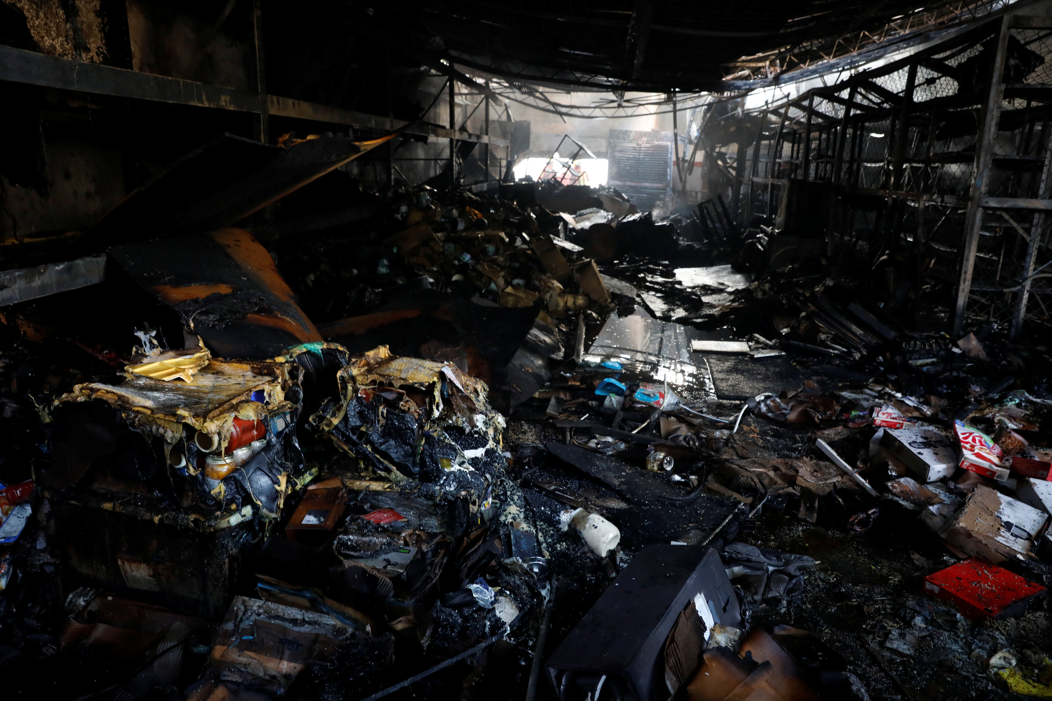 REFILE -CLARIFYING CAPTION  Burned debris are seen in a warehouse in the building where the offices of Venezuelan opposition leader and Governor of Miranda state Henrique Capriles are located, in Caracas, Venezuela, April 8, 2017. REUTERS/Carlos Garcia Rawlins