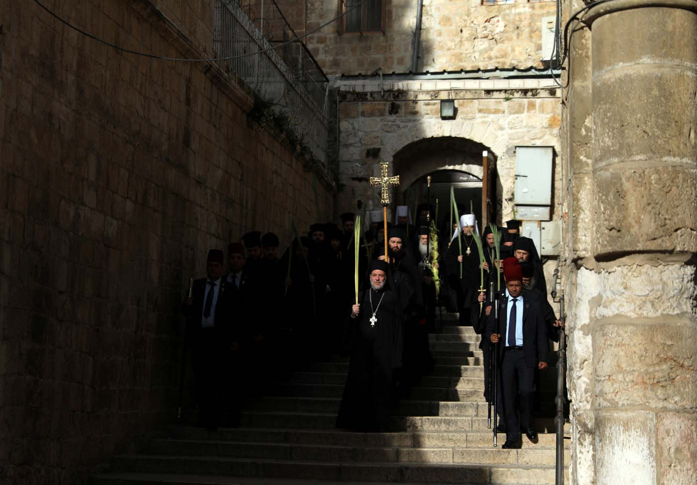 Members of the Orthodox Christian clergy take part in a Palm Sunday ceremony as they walk towards the Church of the Holy Sepulchre in Jerusalem's Old City April 9, 2017. REUTERS/Ammar Awad
