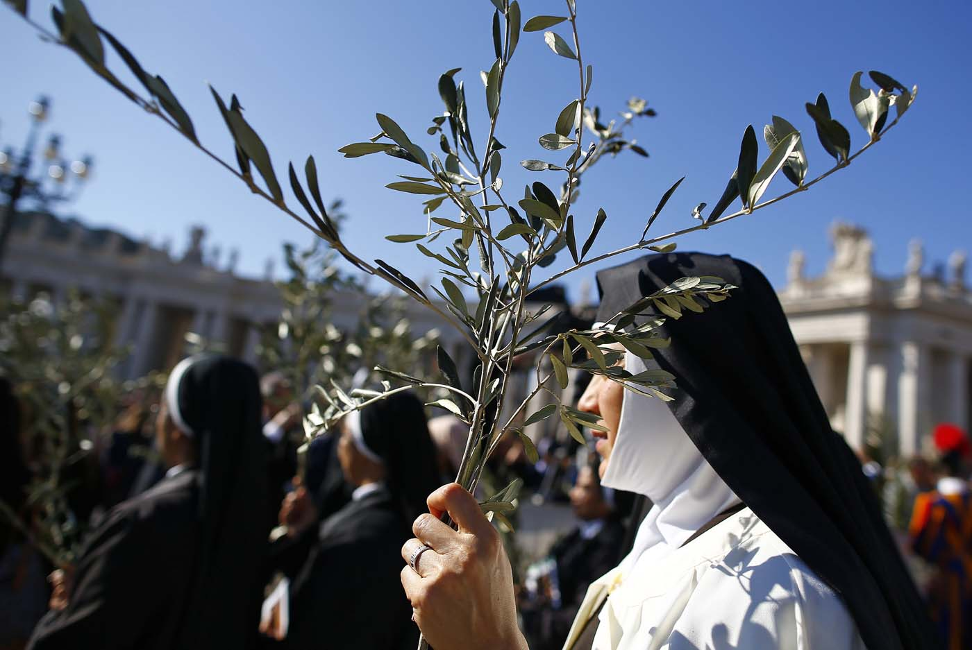 A nun holds a palm during the the Palm Sunday Mass led by Pope Francis in Saint Peter's Square at the Vatican April 9, 2017. REUTERS/Tony Gentile