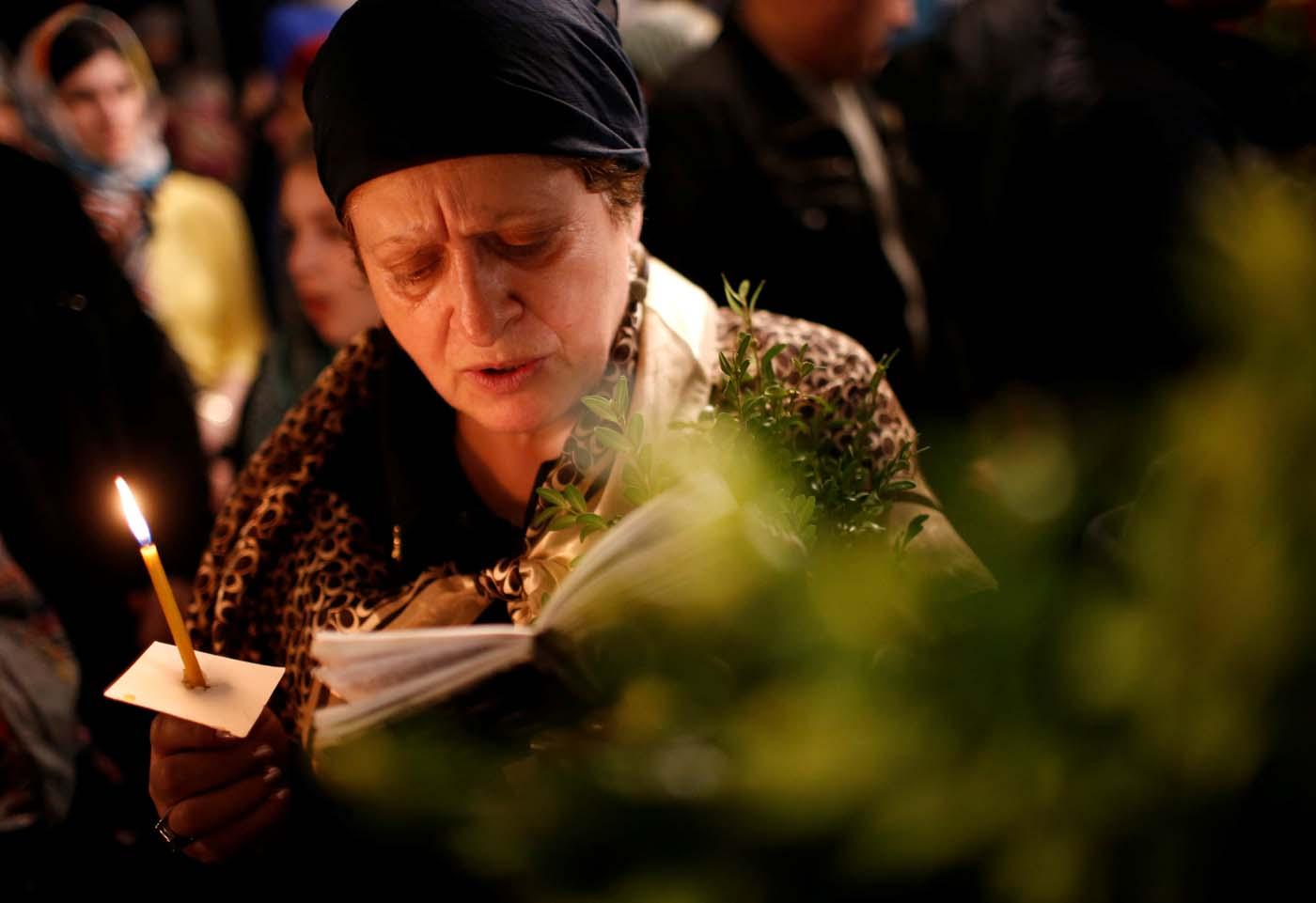 A woman reads a prayer book during the Palm Sunday service in Tbilisi, Georgia April 9, 2017. REUTERS/David Mdzinarishvili