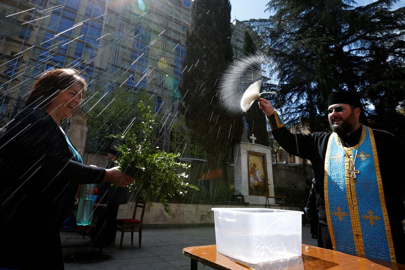 A priest sprays holy water during the Palm Sunday service in Tbilisi, Georgia April 9, 2017. REUTERS/David Mdzinarishvili