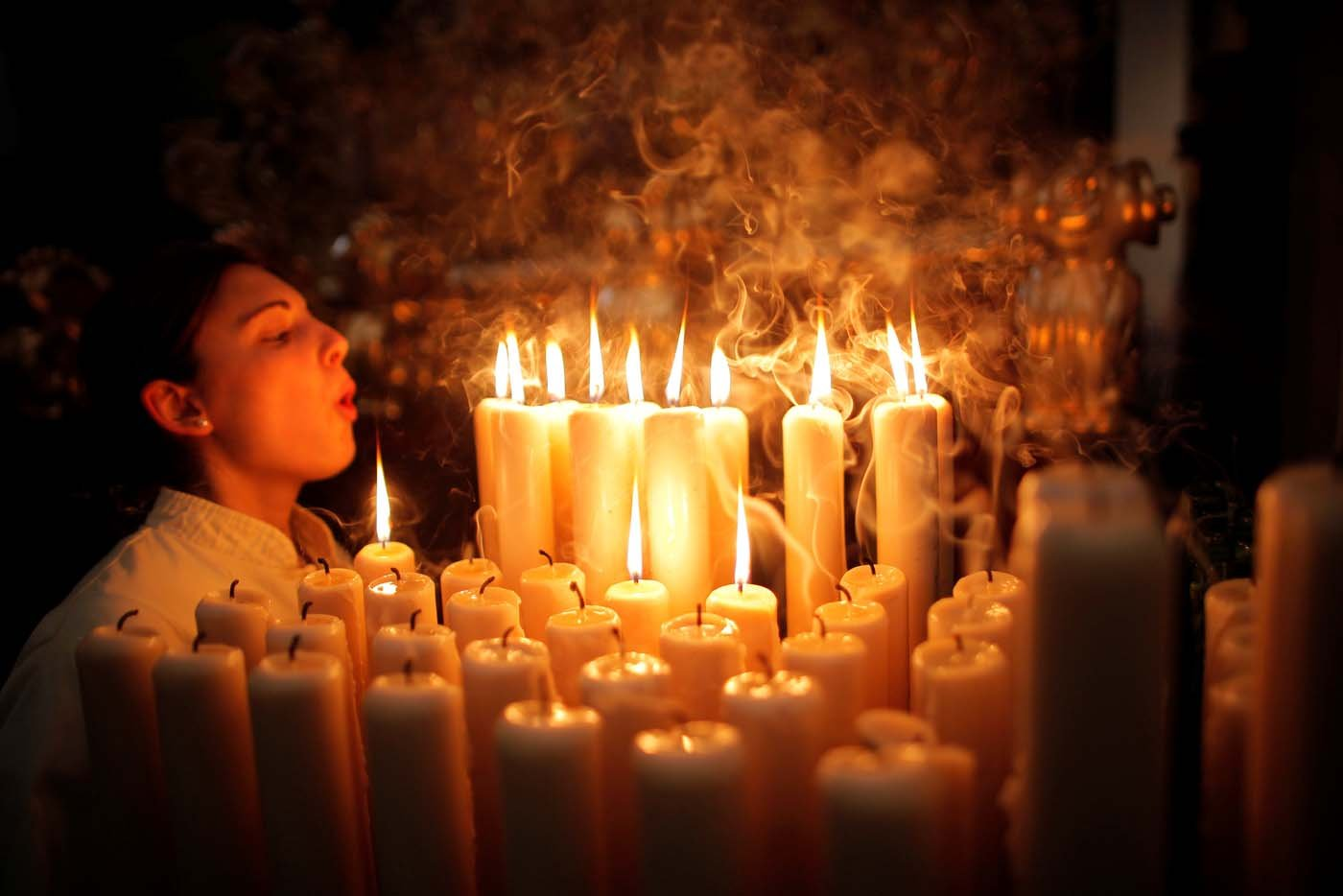 """A penitent of """"Lagrimas and Favores"""" blows out candles inside a church as she takes part in a Palm Sunday procession, marking the start of the Holy Week in Malaga, southern Spain, April 9, 2017. REUTERS/Jon Nazca     TPX IMAGES OF THE DAY"""