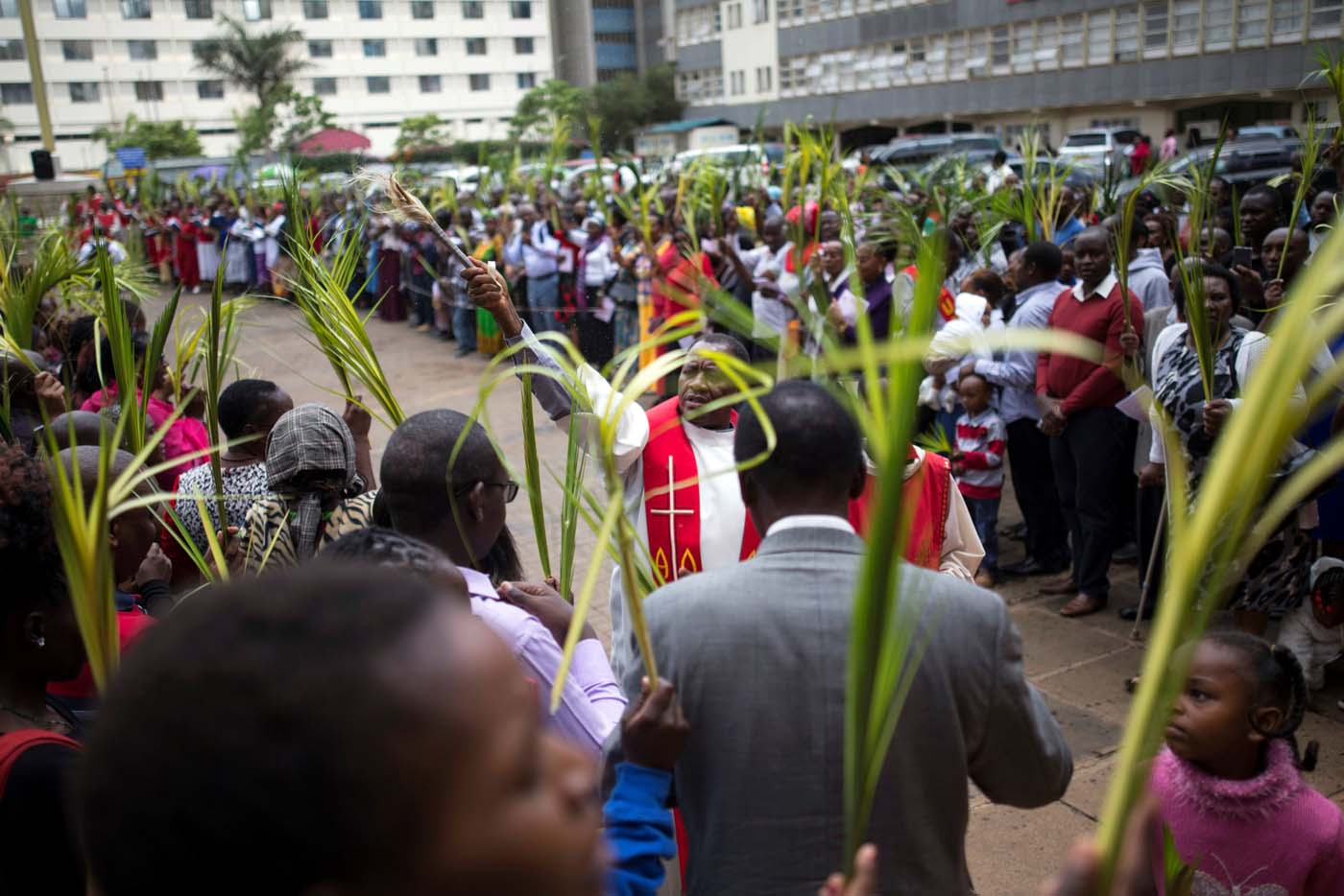 A member of the Catholic Christian clergy blesses worshippers with holy water during a Palm Sunday ceremony in Nairobi, Kenya April 9, 2017. REUTERS/Baz Ratner.