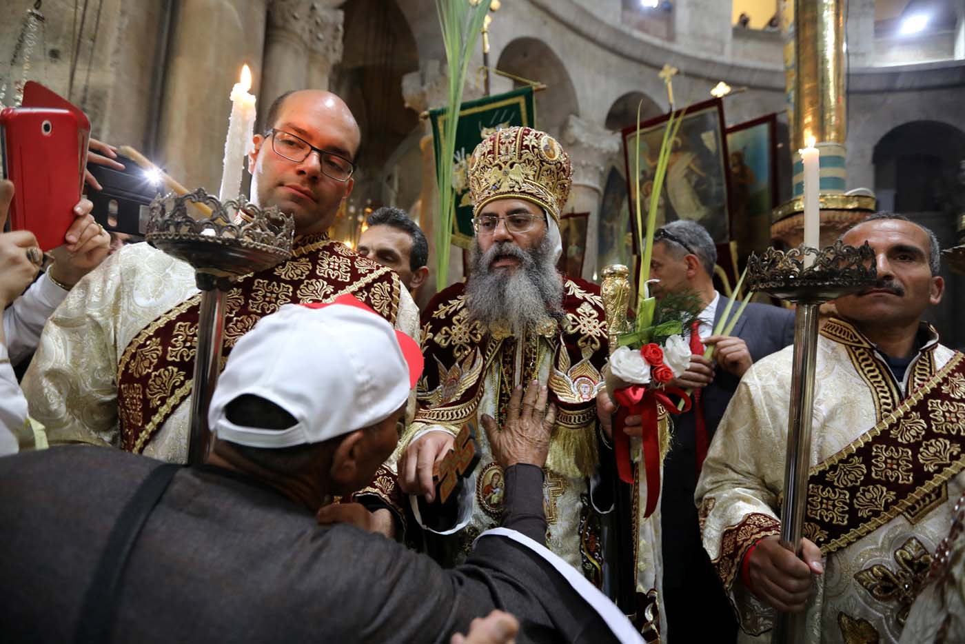 A man touches the Coptic Orthodox Bishop Anthony, during a Palm Sunday ceremony in the Church of the Holy Sepulchre in Jerusalem's Old City April 9, 2017. REUTERS/Ammar Awad