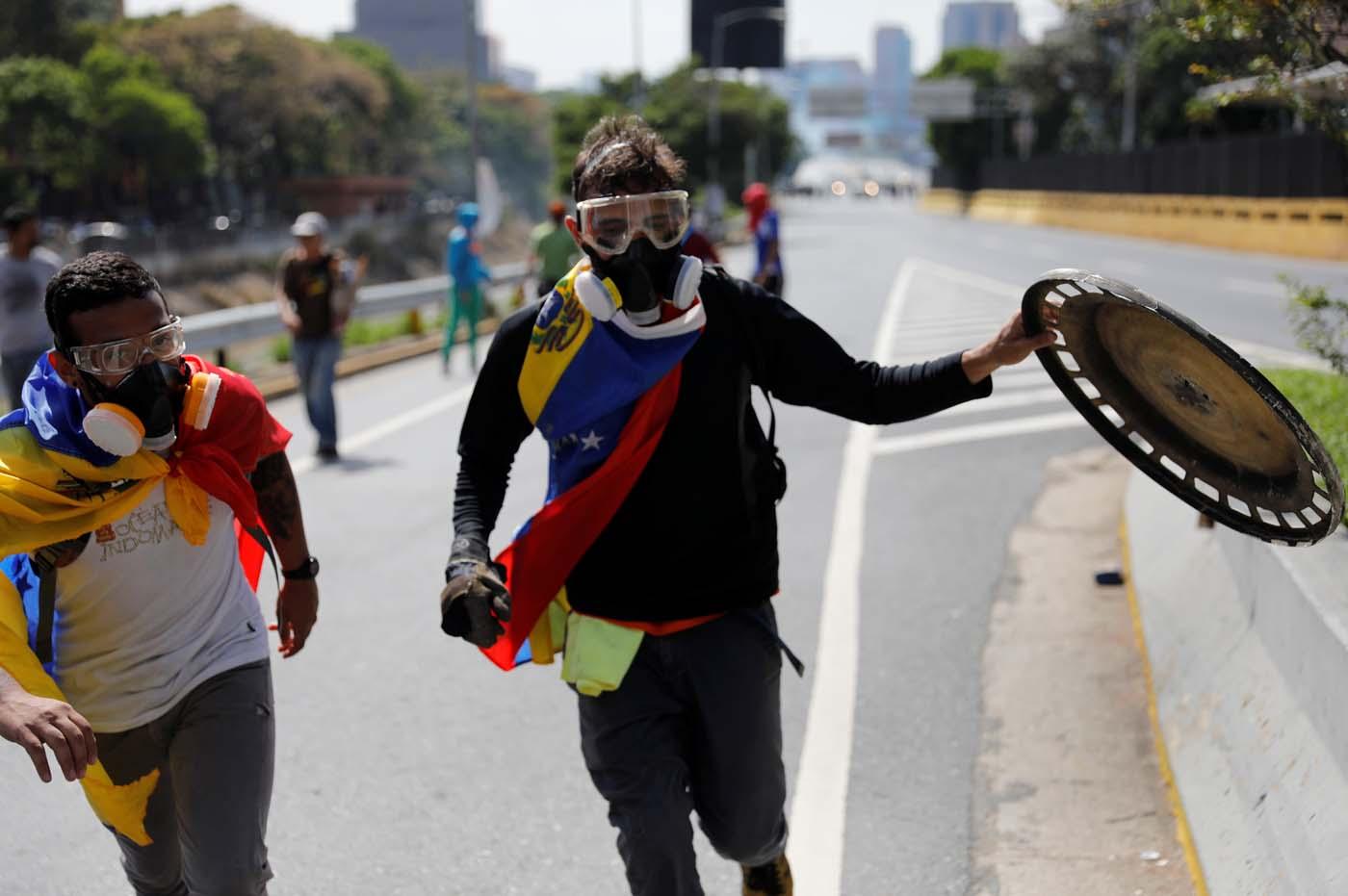 Manifestantes tras un encuentro con la policía en Caracas, abr 10, 2017. Miles de simpatizantes de la oposición venezolana volvieron el lunes a las calles del país petrolero para protestar contra el presidente Nicolás Maduro, al que acusan de haber desvirtuado su gobierno convirtiéndolo en una dictadura. REUTERS/Carlos Garcia Rawlins