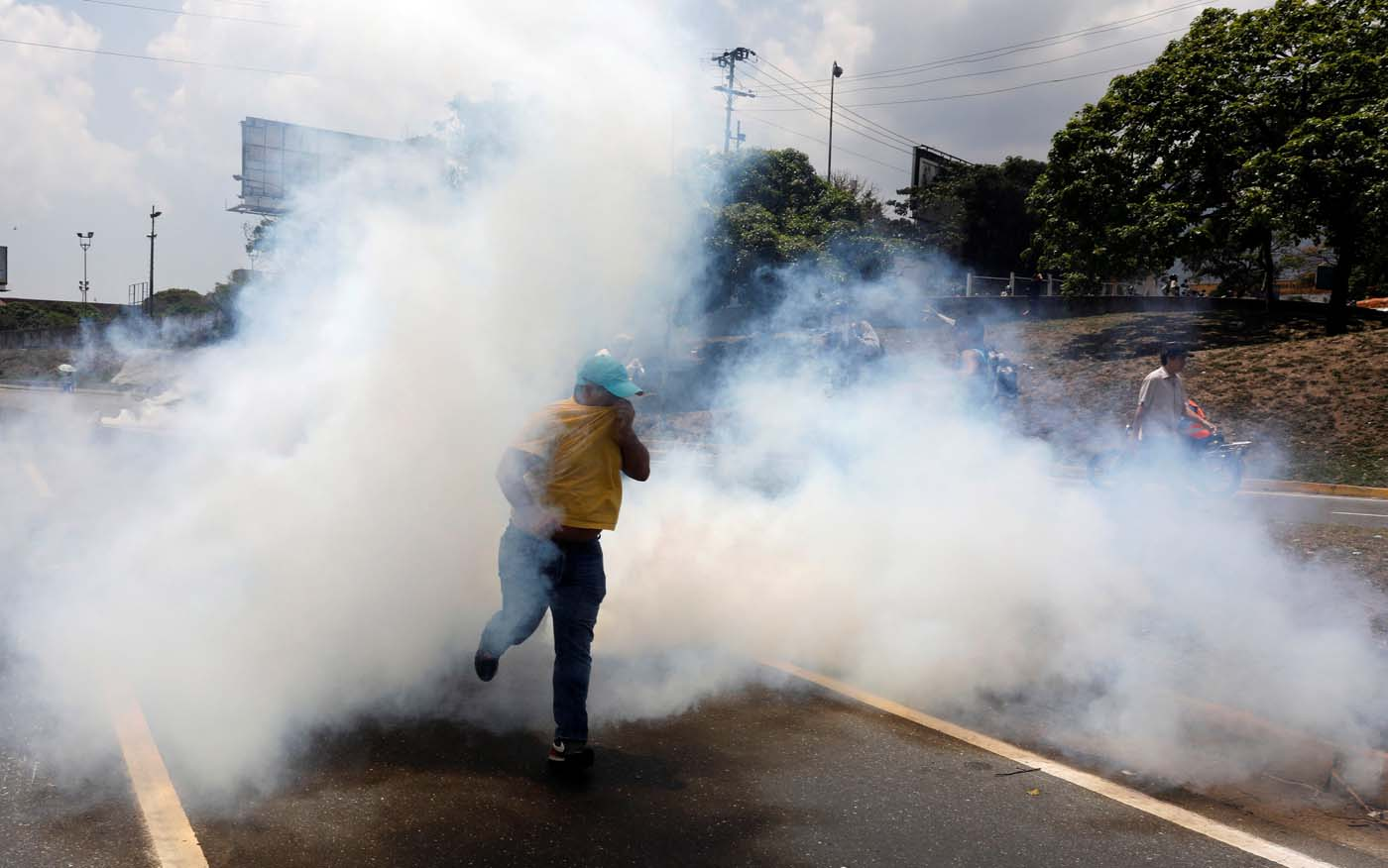 A man runs away from tear gas during a rally against Venezuela's President Nicolas Maduro's government in Caracas, Venezuela April 10, 2017. REUTERS/Carlos Garcia Rawlins