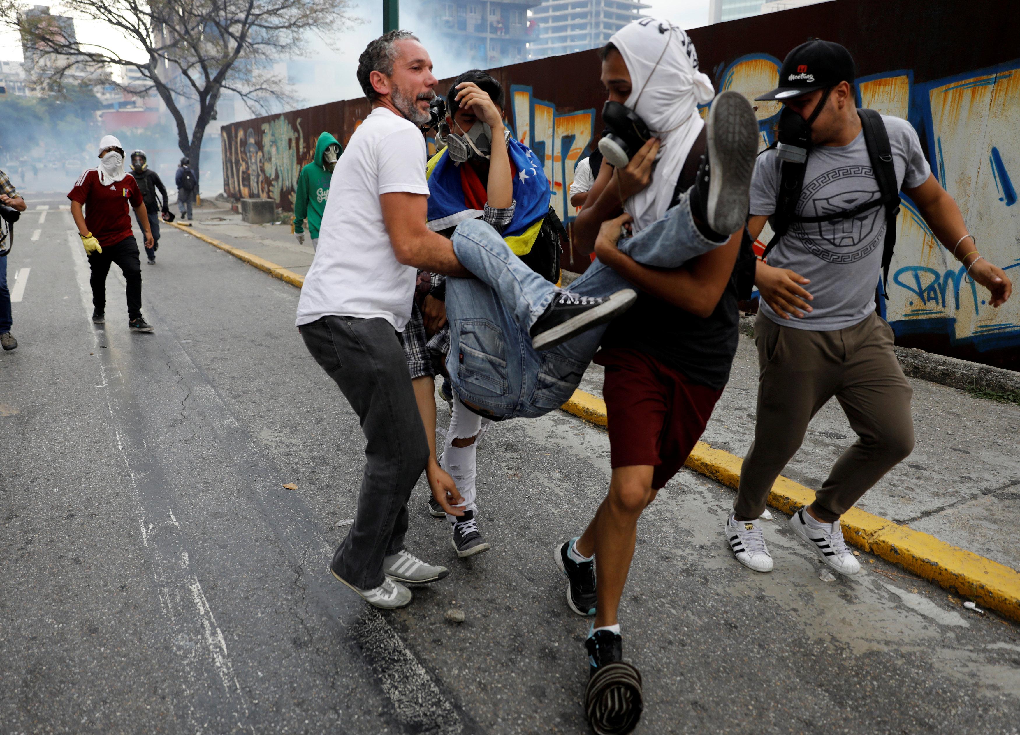 Uno de los afectados por gases lacrimógenos es atendido por compañeros durante una manifestación en abril 10, 2017. REUTERS/Carlos Garcia Rawlins
