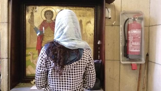 """GRA058. EL CAIRO, 14/04/2017.- Los atentados del pasado Domingo de Ramos en dos catedrales del norte de Egipto, que causaron 46 muertos, no han espantado a los fieles de las iglesias, sino que les han alentado a participar """"más que antes"""" en las misas de Semana Santa. En la imagen, una joven egipcia con la cabeza cubierta reza delante de un retablo que representa un santo copto, en la iglesia de San Pedro, en el complejo de la catedral de El Cairo, en el barrio de Al Abasiya, donde cientos de cristianos se han acercado a participar en las oraciones, a pesar de que ese mismo templo fue blanco de otro ataque terrorista el pasado diciembre, que dejó una treintena de muertos, la mayoría mujeres y niñas. EFE/Azza Guergues"""