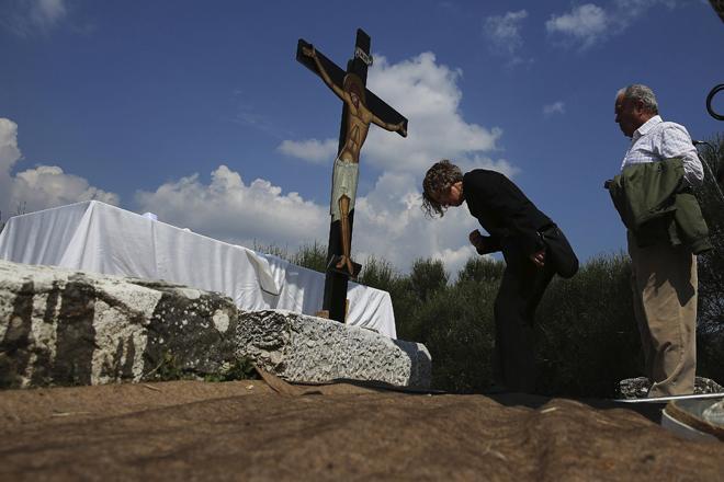 QBV196 ATENAS (GRECIA) 14/04/2017.-Varios fieles hacen cola para besar un crucifijo durante el ritual Apokathelosis, de recreación de la bajada de Jesús de la cruz, en la iglesia del monasterio Pendeli en Atenas (Grecia) hoy, 14 de abril de 2017. EFE/Alexandros Vlachos