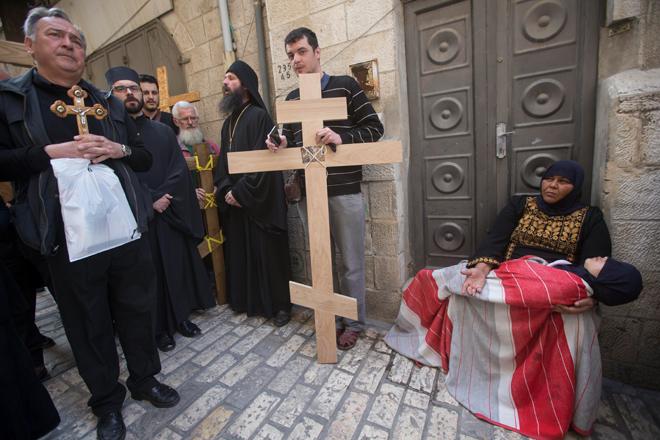 ATS16 JERUSALÉN (ISRAEL) 14/04/2017.- Una mujer musulmana con su hijo en brazos pide limosna al paso de varios creyentes cristianos que partiicpan en una procesión de Viernes Santo por la Vía Dolorosa en el casco viejo de Jerusalén (Israel) hoy, 14 de abril de 2017. EFE/Atef Safadi