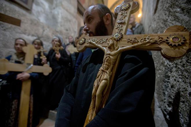 ATS15 JERUSALÉN (ISRAEL) 14/04/2017.- Un fiel carga con una cruz durante una oración en la Iglesia del Santo Sepulcro tras finalizar una procesión de Viernes Santo por la Vía Dolorosa en el casco viejo de Jerusalén (Israel) hoy, 14 de abril de 2017. EFE/Atef Safadi