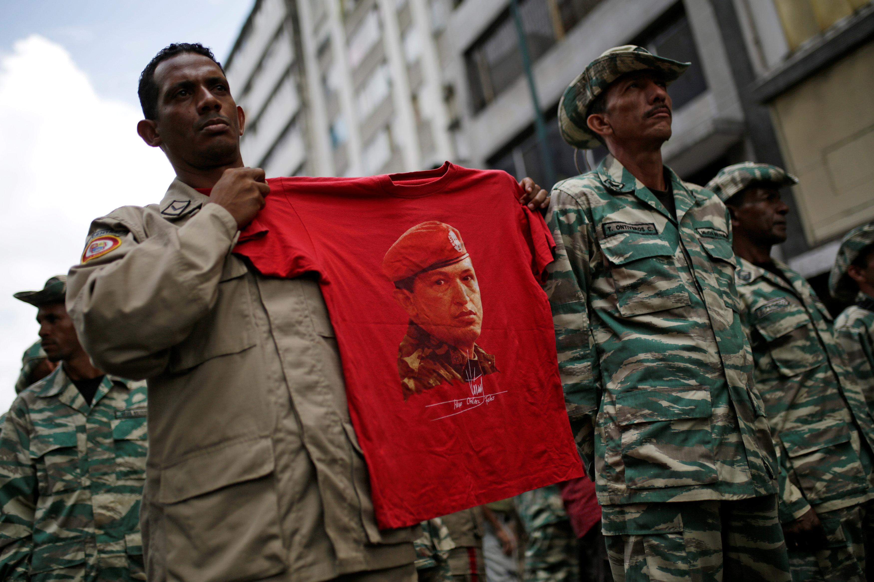A militia member holds a t-shirt with an image of Venezuela's late President Hugo Chavez during a ceremony with Venezuela's President Nicolas Maduro at Miraflores Palace in Caracas, Venezuela April 17, 2017. REUTERS/Marco Bello
