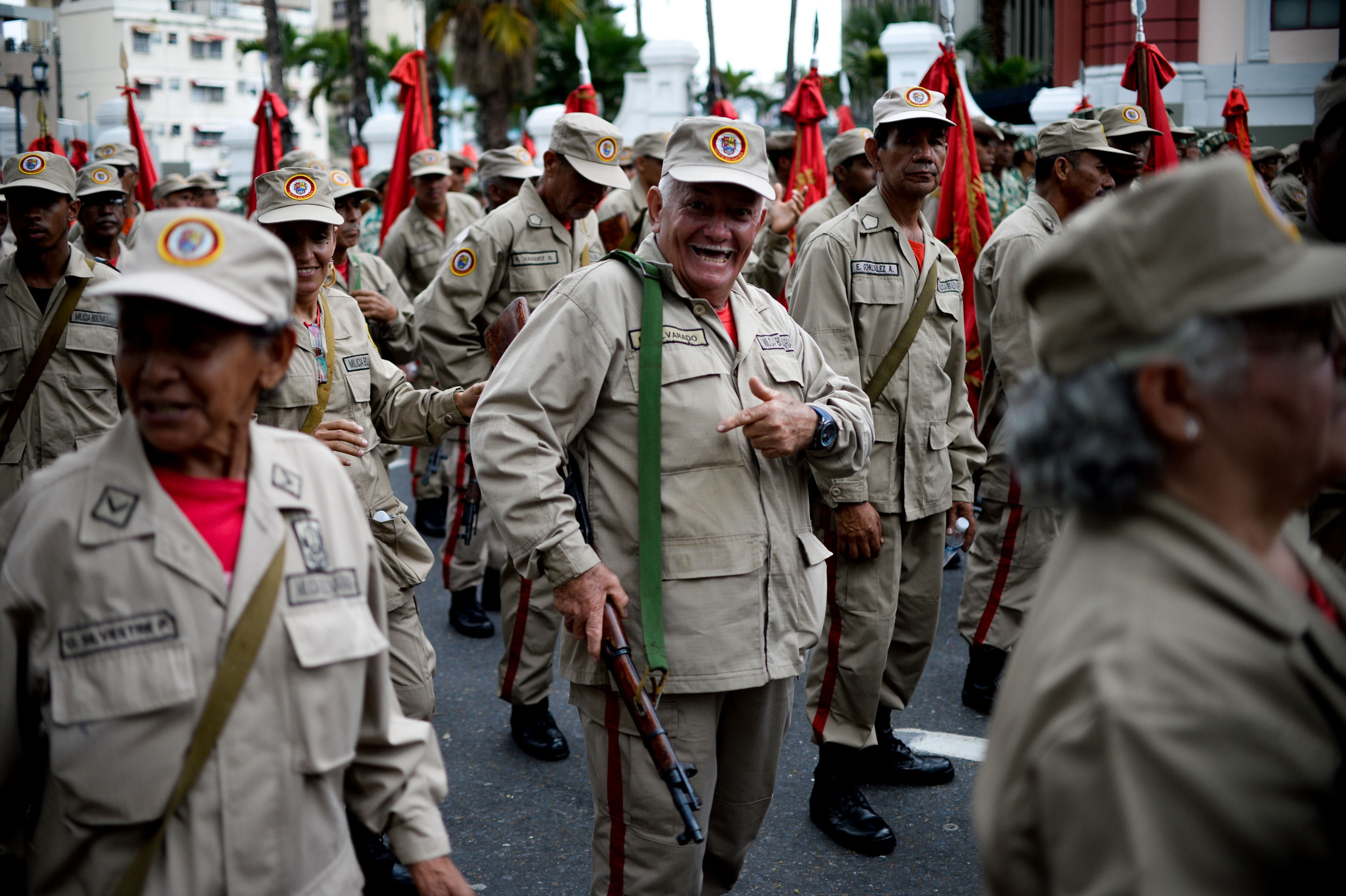 """Members of the Bolivarian Militia take part in a parade in the framework of the seventh anniversary of the force, in front of the Miraflores presidential palace in Caracas on April 17, 2017. Venezuela's defence minister on Monday declared the army's loyalty to Maduro, who ordered troops into the streets ahead of a major protest by opponents trying to oust him. Venezuela is bracing for what Maduro's opponents vow will be the """"mother of all protests"""" Wednesday, after two weeks of violent demos against moves by the leftist leader and his allies to tighten their grip on power. / AFP PHOTO / Federico PARRA"""